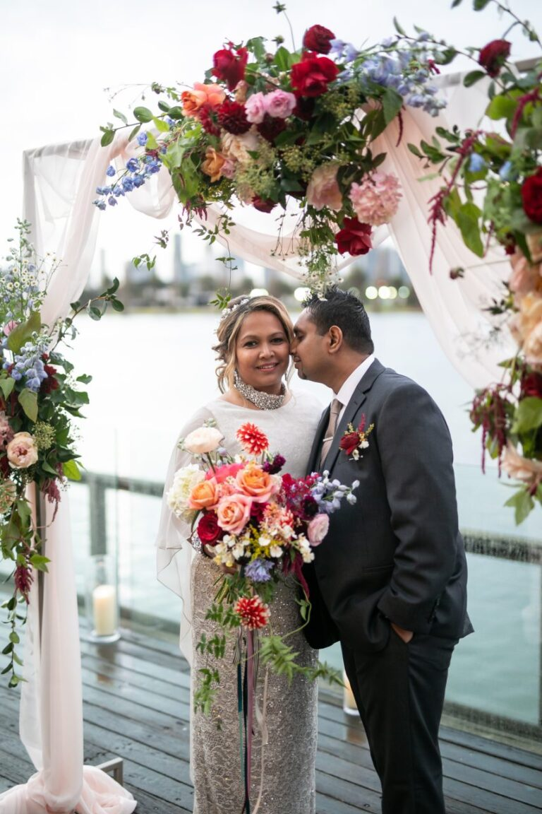 bride and groom with wedding arch